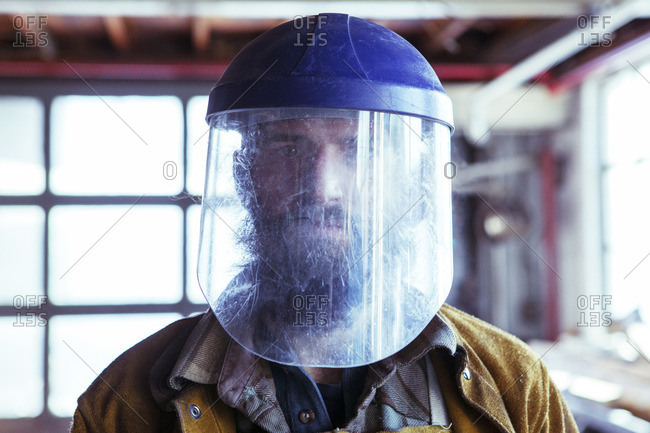 Portrait of worker in protective mask in factory