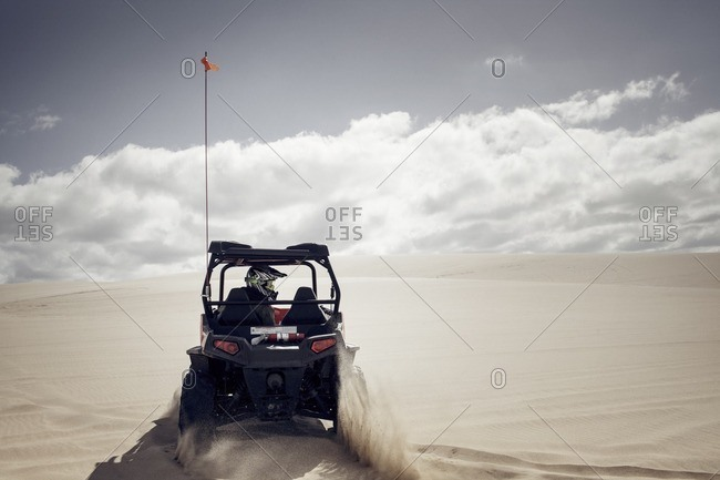Man driving golf cart on sand at desert against cloudy sky