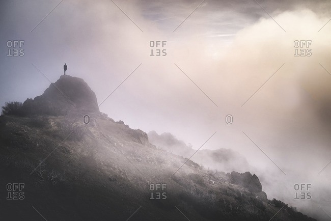 Solitude man standing on mountain during foggy weather