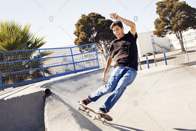 Man skateboarding on sports ramp in park against clear sky