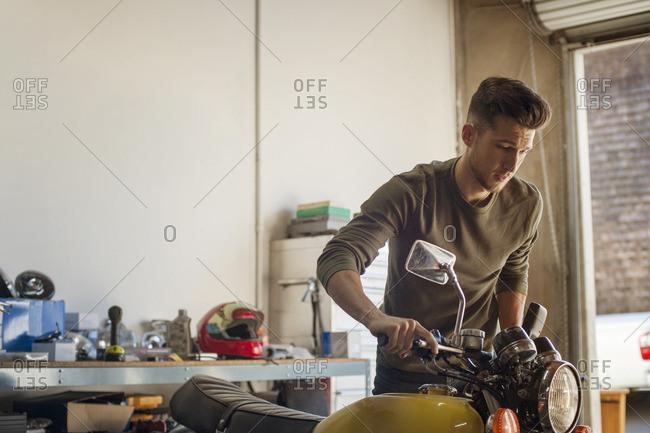 Man examining motorcycle in garage
