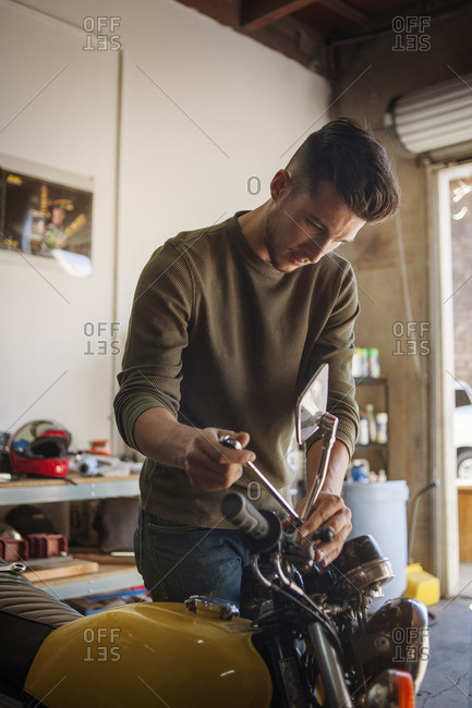 Man adjusting motorcycle in garage