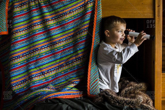 Curious boy looking through telescope while standing on bunkbed
