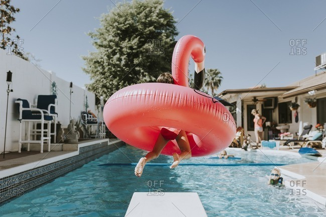 Rear view of girl jumping with rubber duck in swimming pool