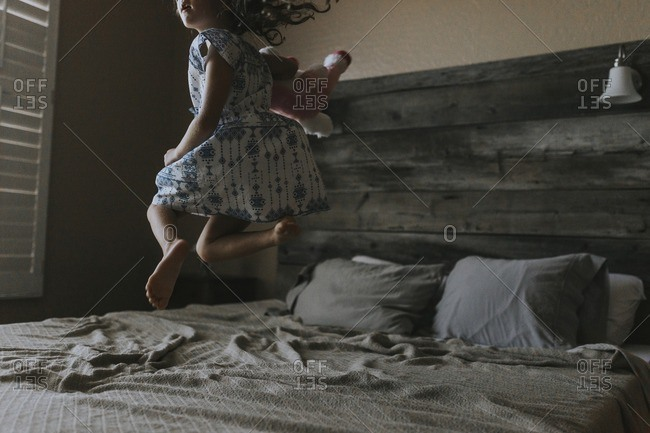 Cheerful girl jumping on bed at home