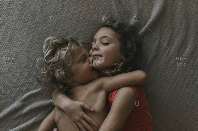 High angle view of loving siblings embracing while relaxing on bed