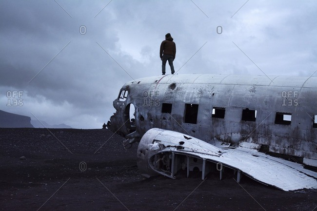 Rear view of man standing DC-3 airplane against cloudy sky