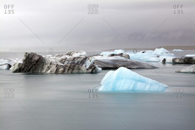 Glaciers in sea against cloudy sky