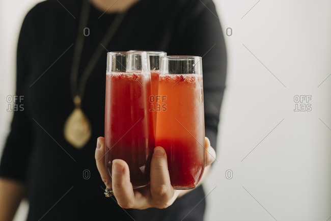 Midsection of woman holding cocktail while standing against wall at home