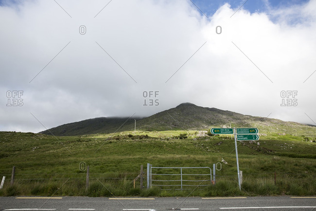 Gate and information sign on grassy field against cloudy sky