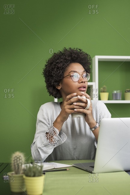 Thoughtful woman with laptop computer having coffee at office