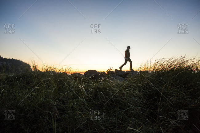 Silhouette of distant Caucasian man walking on rocks at sunset