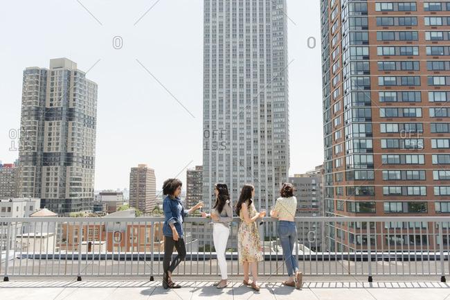Women drinking wine on urban rooftop