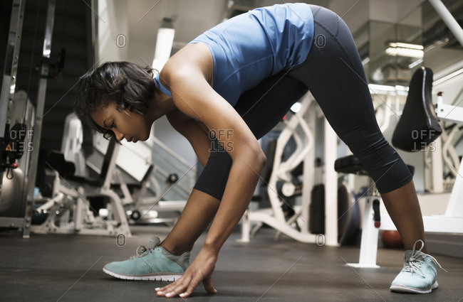 Mixed Race woman stretching legs at gymnasium