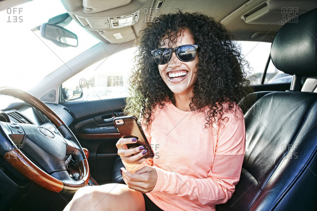 Laughing Hispanic woman in car holding texting on cell phone
