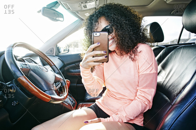 Smiling Hispanic woman in car posing for cell phone selfie