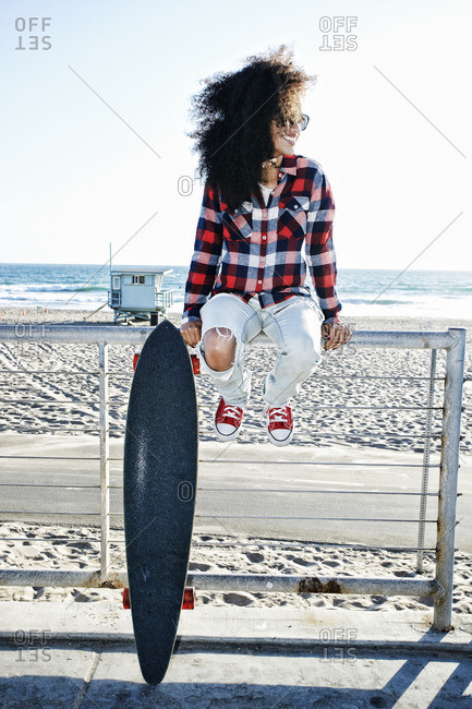 Hispanic woman sitting on fence at beach with skateboard