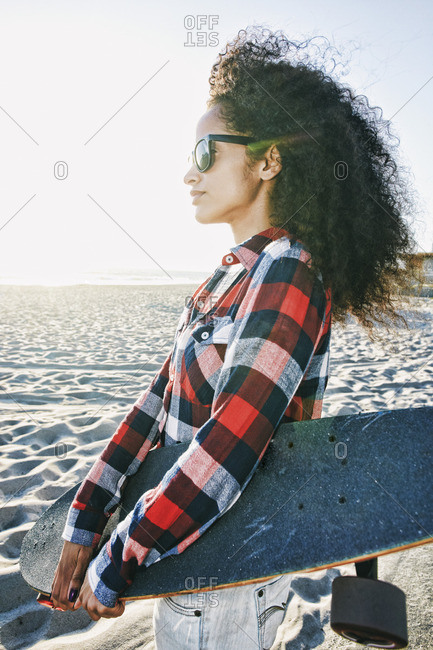 Hispanic woman holding skateboard at beach