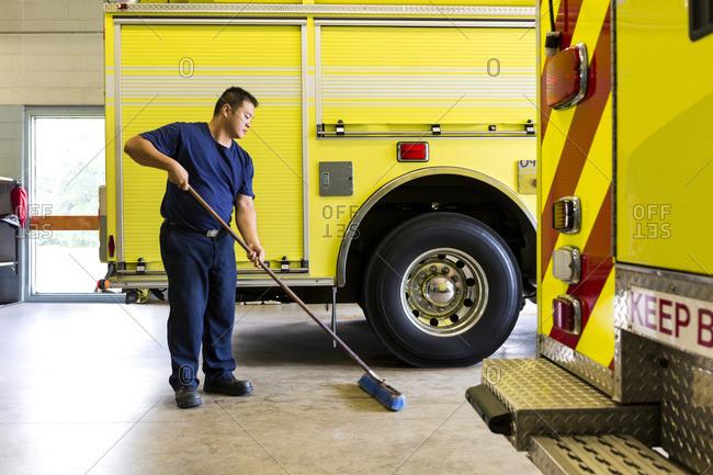 Chinese fireman sweeping floor near fire trucks