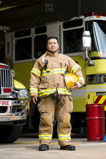 Serious Chinese fireman posing near fire trucks