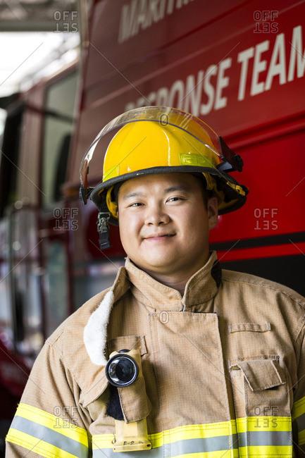 Smiling Chinese fireman standing near fire truck
