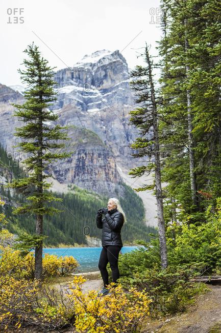 Caucasian woman using binoculars at mountain lake