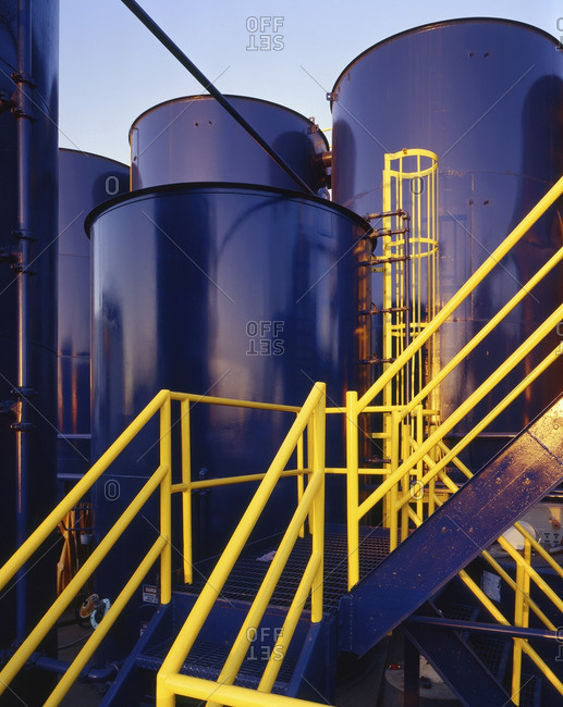 Yellow banisters on staircase near blue storage tanks