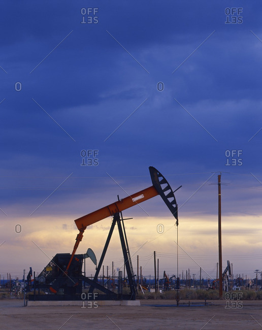 Oil rig drilling at sunset