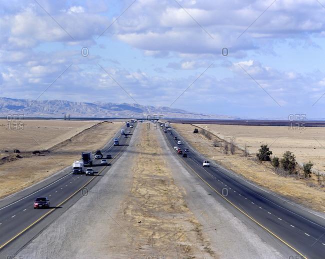 Cars and semi-trucks driving on freeway