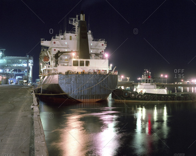 Tugboat and ship moored in harbor