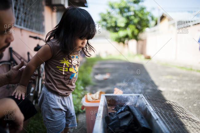Young boy with man watching a grill