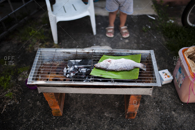 Fish cooking on banana leaf on grill