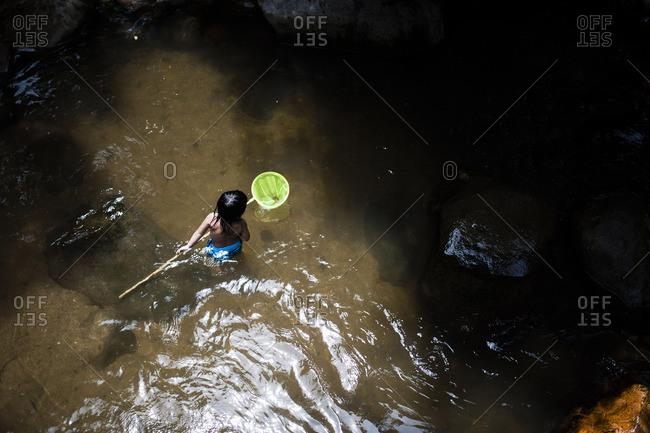 Boy wading in stream holding net