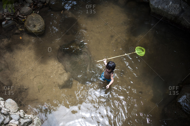 Boy wading in a stream holding net