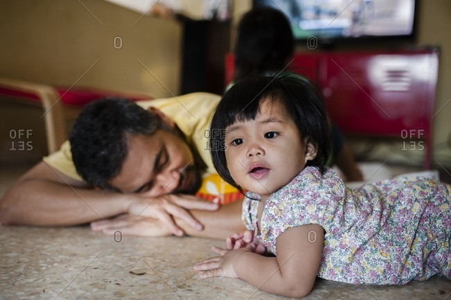 Dad lying next to toddler on floor