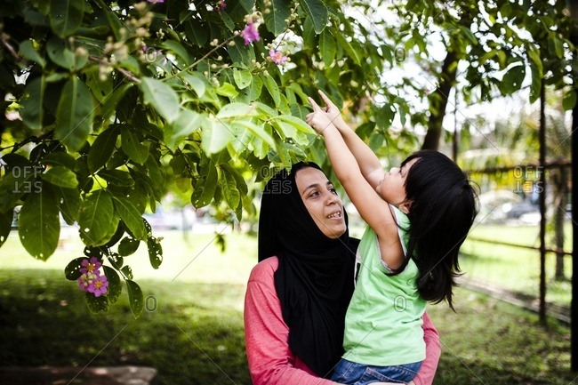 Mom lifting boy to pick flowers from tree