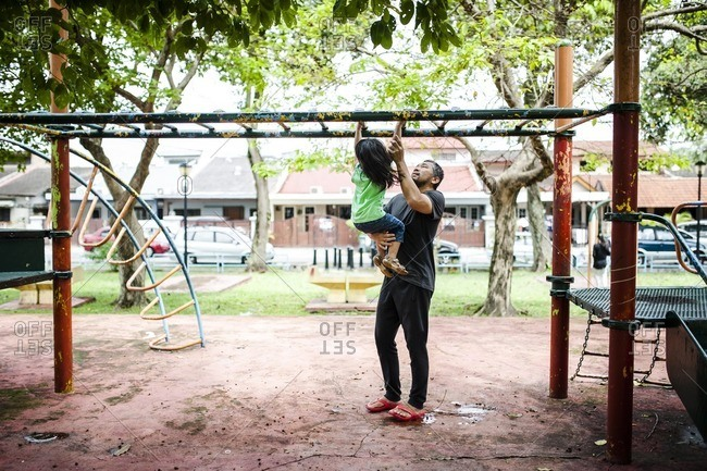 Man helping boy on monkey bars