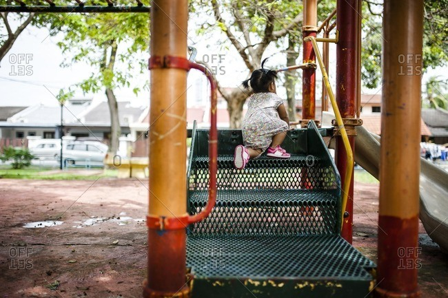 Toddler girl climbing up jungle gym