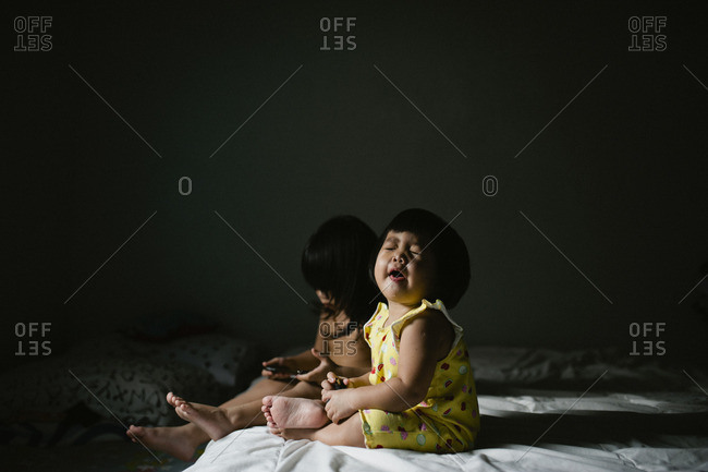 Toddler boy and sister on bed together