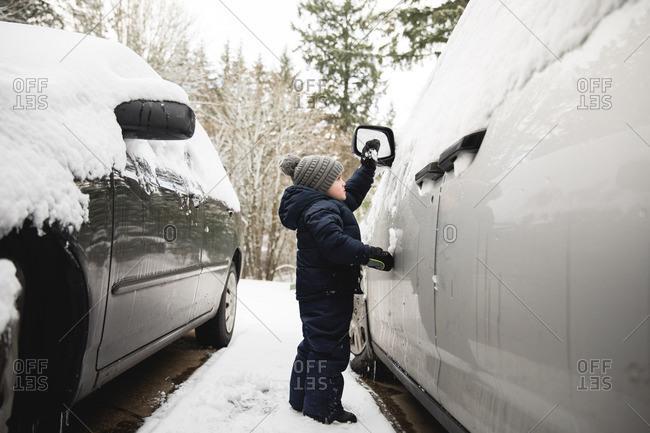 Boy standing outside car in winter