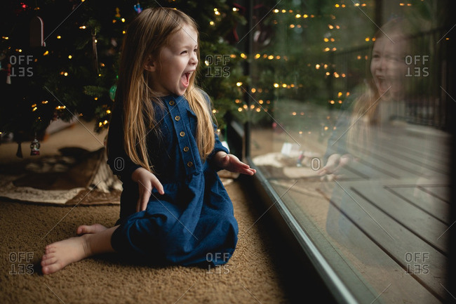 Excited girl by window at Christmastime