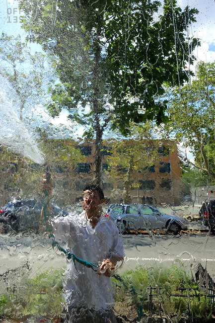 Man cleaning a window with a hose