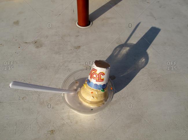 Cone of ice cream melting in bowl
