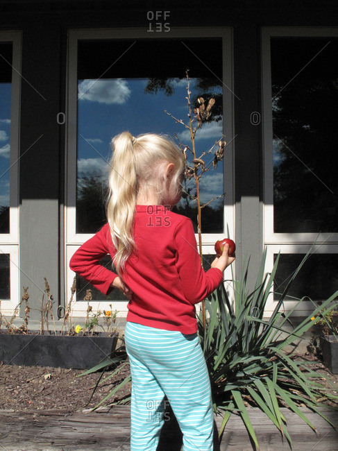 Girl with blonde ponytail holding apple
