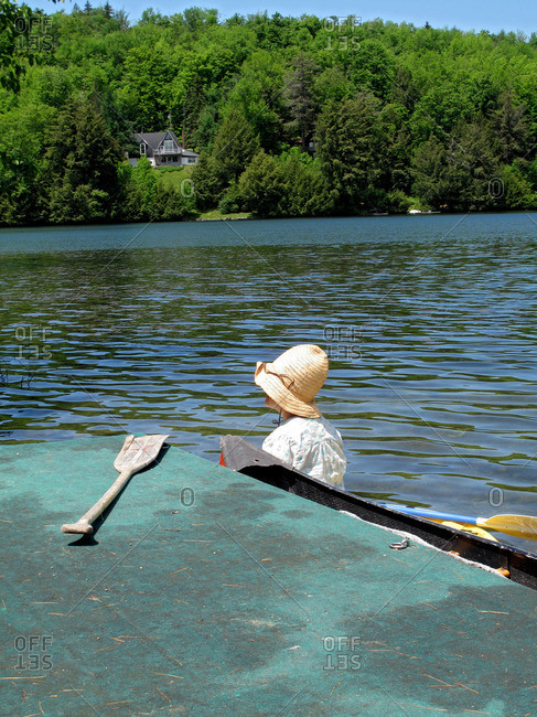 Woman wears a tall straw hat that obscures her face while sitting in a canoe next to an old dock with an ore, Vermont