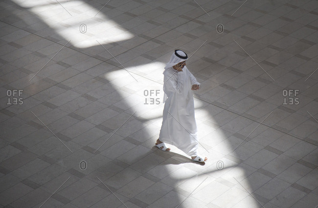 Dubai, UAE - September 16, 2012: Man in Burj mall on cell phone