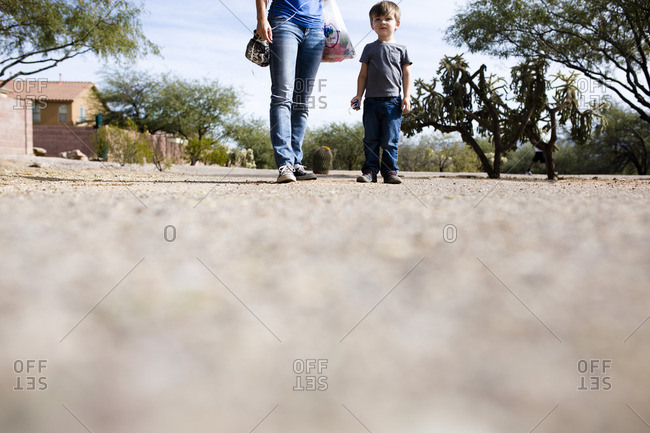 Ground level view of toddler boy walking with woman