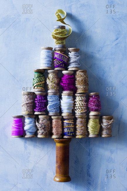 Wooden spools of ribbon and trim arranged in the shape of a tree