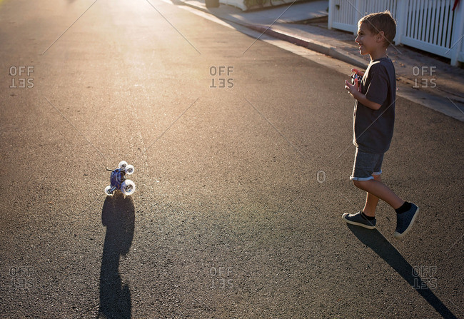 Boy with remote control car in sunny street