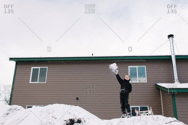 Boy throwing snow in his backyard